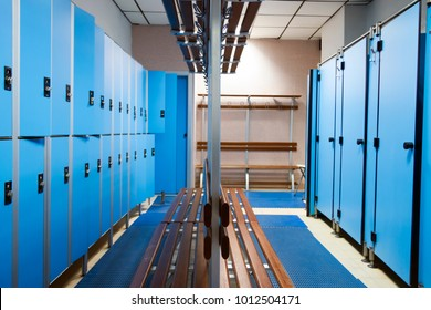 an empty locker room in the sports club, school, section. line lockers with numbers and locks and a shower. in the center a wooden clothes hanger and a dressing-gown