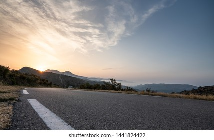 Empty long road on a sunny summer day at bright sunset
