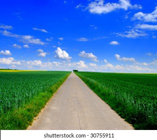 Empty long road through a green field with blue sky and clouds