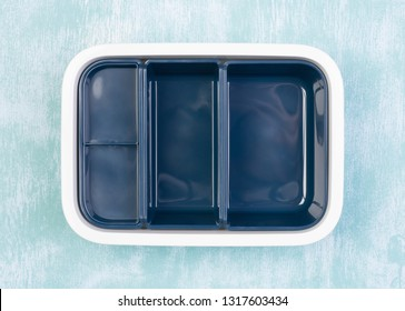 Empty lunch box on blue background, top view