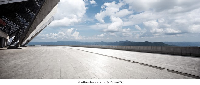 empty marble floor and green hill in blue cloud sky