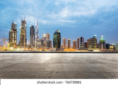 empty marble floor and modern buildings in midtown of dubai in cloud sky at twilight