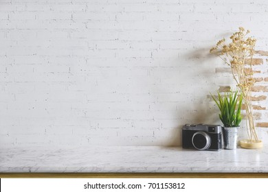 Empty marble top table with vintage camera and houseplant over white brick wall. Copy space for products display montage.