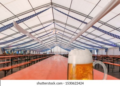empty marquee for the Oktoberfest, on a wooden table stands the first glass of beer