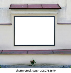 An empty message board hangs on the ruined yellow plastered  wall of an old church.  Billboard area isolated on white