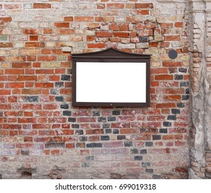 An empty message board hangs on the ruined brick wall of an old church.  Billboard area isolated on white