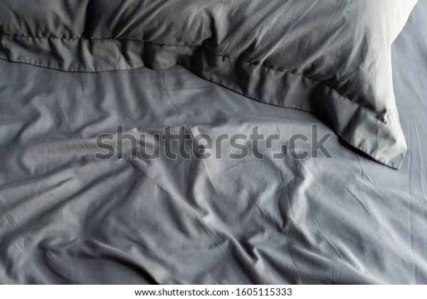 Empty messy dark gray bed with pillows