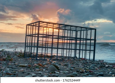 Empty metal cage on the sunset rocky beach