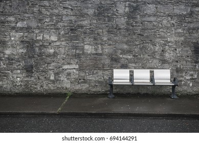Empty metal chairs in Sligo Town in Ireland at a bus stop against a grey brick wall on the road