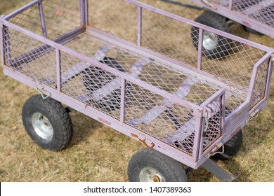 An empty metal pink wagon on dry grass next to another wagon near a farm.