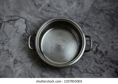 Empty metal pot in the kitchen on marble table. Top view.