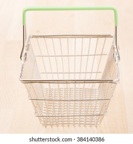 Empty metal shopping basket on wood surface. Conceptual image of retail store, sale and commerce.