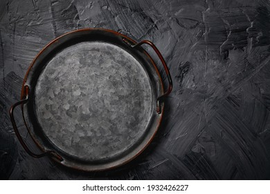 Empty metal tray on a grey background. Space for text.