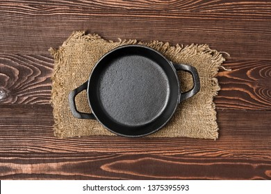 Empty mini cast-iron skillets on wooden table, view from above