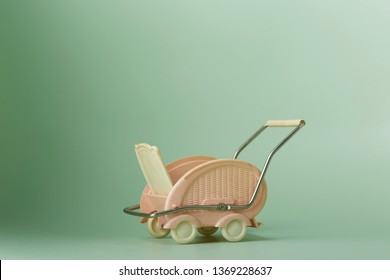 empty miniature plastic vintage baby stroller pink and white 1950ies style on green backround