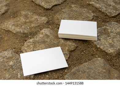 empty mockup business cards stacked on cobblestone flooring