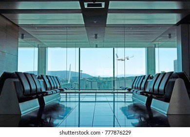 An empty modern airport departure lounge with seating and plane taking off in the background