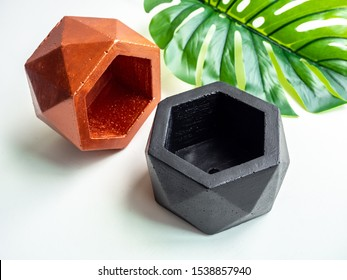 Empty modern black and copper colors geometric concrete planters with palm leaf isolated on white background with copy space. Beautiful painted concrete pots.