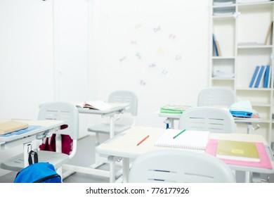 Empty modern classroom without schoolchildren by desks during break