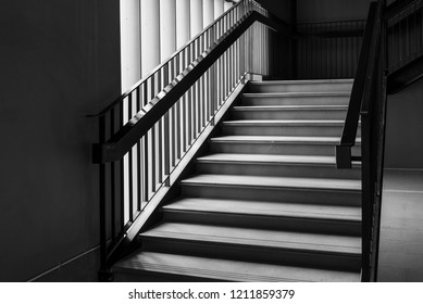 Empty Modern Concrete Staircase and black steel handrail with natural light, staircase in modern building - Dark Tone