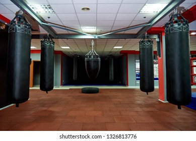 Empty modern fight club with punching bags of different shapes for practicing martial arts.