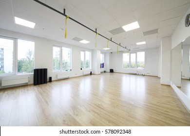 Empty modern hall for fitness and pilates with big windows, wooden floor