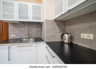 Empty modern kitchen countertop with sink and kettle