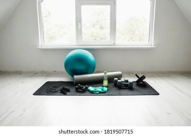 Empty modern white bright room with home workout accessories equipment. Yoga ball, resistance exercise latex band, foam roller, weights, jump rope, water bottle. Black and white colors.