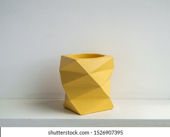 Empty modern yellow geometric concrete planter isolated on white background. Beautiful painted concrete pot.