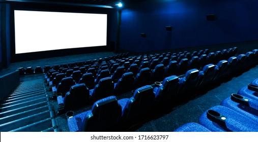 Empty movie theatre interior with screen and seats.