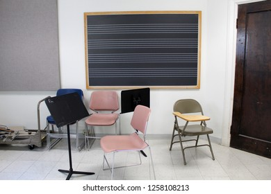 An empty music classroom with scattered chairs