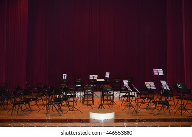 Empty music stand and chairs on stage