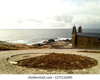 Empty Muxia beach at end of Camino de Santiago and Camino Finisterre, with ocean waves crashing against shore