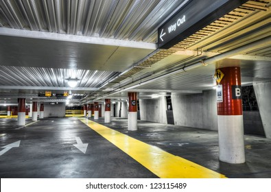 Empty new parking interior with red and white columns and yellow pedestrian walkway.