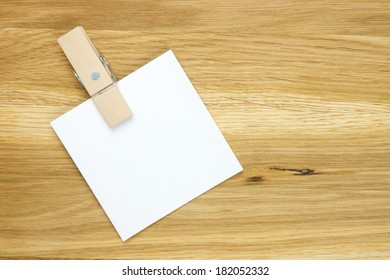 empty note with clothes-peg on wooden surface