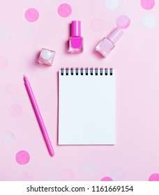 Empty note pad and colorful nail polishes on pink confetti background. Copyspace for text. Bright and festive picture. Top view, flat lay.