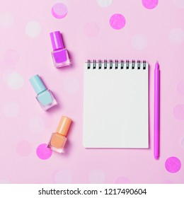 Empty note pad and colorful nail polishes on pink pastel confetti background. Copyspace for text. Bright and festive picture. Top view, flat lay.