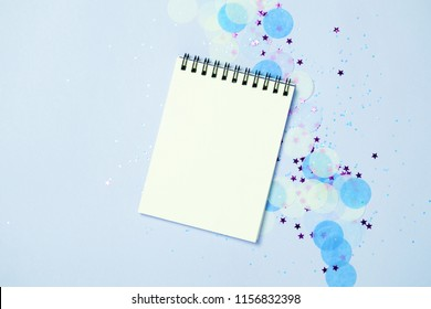 Empty note pad on festive confetti blue backgroung. Top view, flat lay. Office holiday concept.
