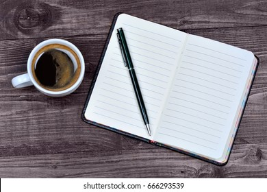 Empty notebook with coffee cup on wooden background close-up