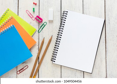 Empty notebook and colorful pencils on white wooden table