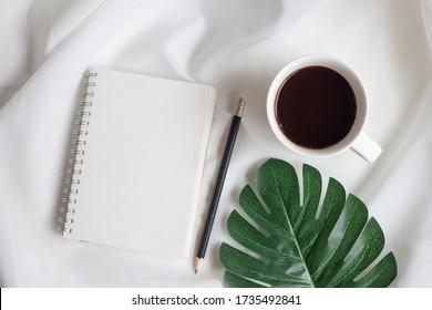Portable vide avec tasse de café et feuille de monstère sur fond de tissu blanc. Vue en haut, couche plate.