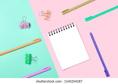 Empty Notebook or notepad on pink and blue background. Creative minimalism chancery concept. Top view, flat lay.