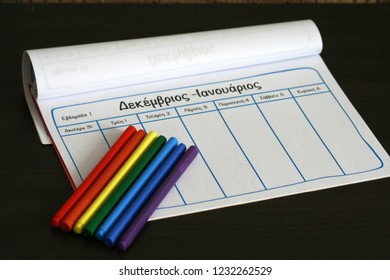 """Empty notebook page and 7 multicolored markers. Translation of the Greek words on the page: """"December - January, Week 1, Monday 31, Tuesday 1, Wednesday 2, Thursday 3, Friday 4, Saturday 5, Sunday 6"""""""