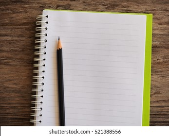 Empty notebook paper for text with black pencil on wooden background.