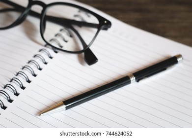 Empty notebook paper for text with pen on wooden background.