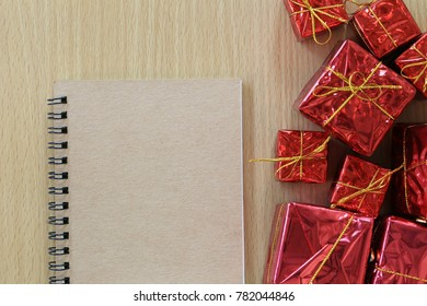 Empty notebook placed near the red gift box on a brown wooden floor and have copy space to input ideas of your work.