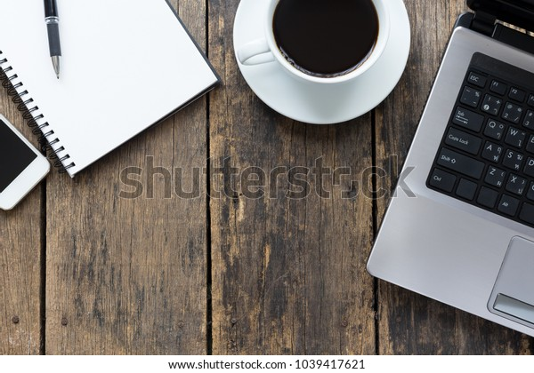empty notebook with smart phone and computer on wooden table ,top view