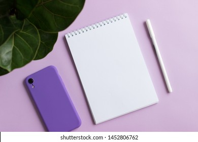 An empty notebook, a smartphone in a violet case, a white pen on a purple background. White page, top view, flat lay.