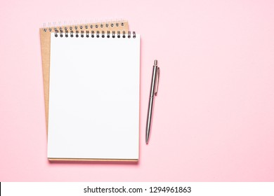 Empty notepad and pen on pink  background. Trendy office Flat lay background with copy space.