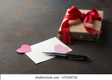 Empty notepad with pen and pink hearts on dark retro background, Gift box. Valentines day Romantic concept. Selective focus